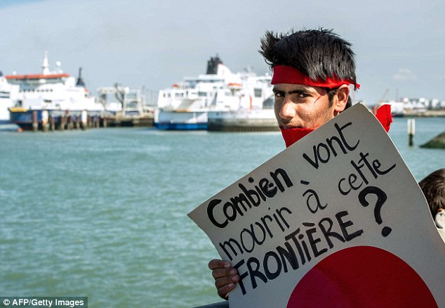 Protest: Migrants and their supporters marched through Calais port today. This poster asks how many more are going to die at this frontier - 10 people have already died trying to cross into the UK