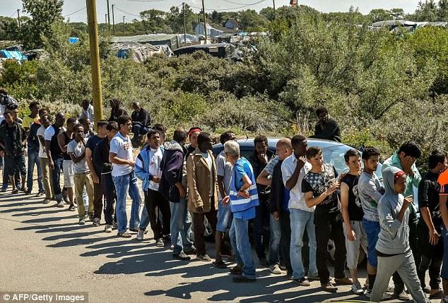 Colas: Migrantes en espera de alimentos dádivas en la 'jungla' campo de refugiados en Calais