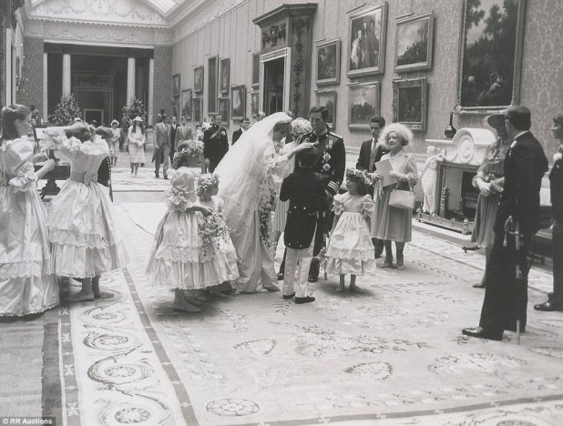 Reception: The newly-married couple stop to speak to their page boys and bridesmaids as the Queen Mother (right) looks on