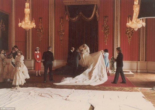 Iconic: With thousands of pearls and a 25ft train, Diana's wedding dress is carefully maneuvered into position for an official photograph