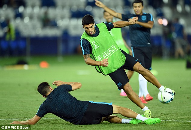 Former Liverpool striker Luis Suarez does his best to swerve an over-zealous slide tackle in training