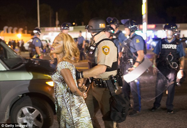 The appearance of the four men quickly drew stares in the mostly black neighborhood, which exploded into violence again on Sunday night. A woman is pictured being arrested during the protests
