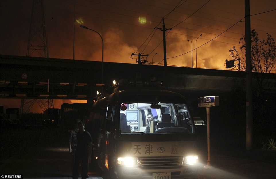 On the scene: Rescuers are seen in a van near the site of the blasts in Tianjin municipality yesterday evening