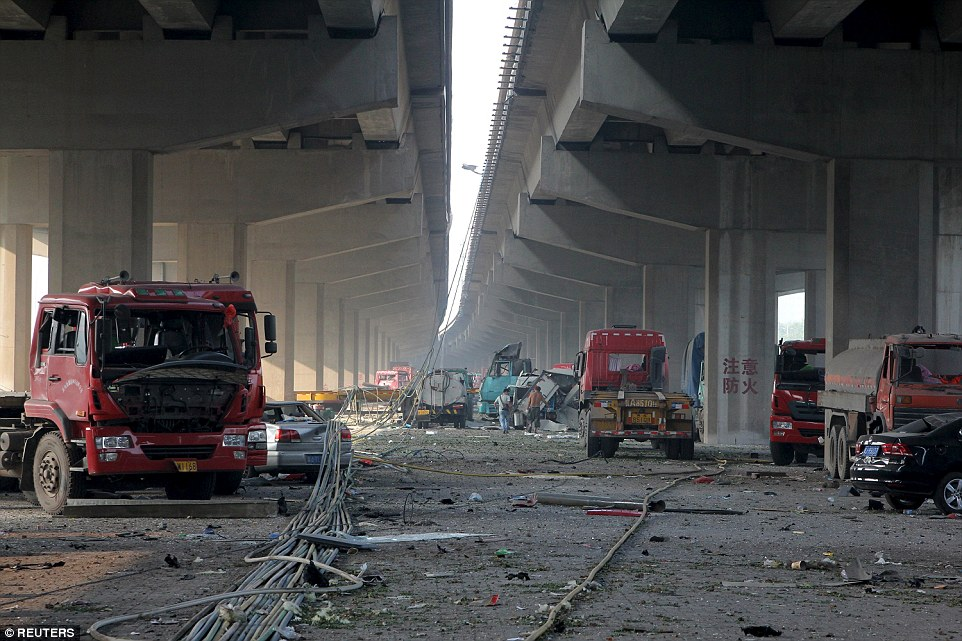 Blasts: Damaged vehicles are seen under bridges close to the site of the explosions at Binhai new district, Tianjin, early this morning