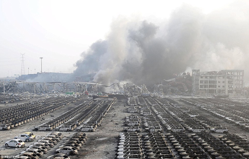 Charred: Damaged cars are seen as smoke rises from the debris after the explosions at the Binhai new district in Tianjin, China, last night