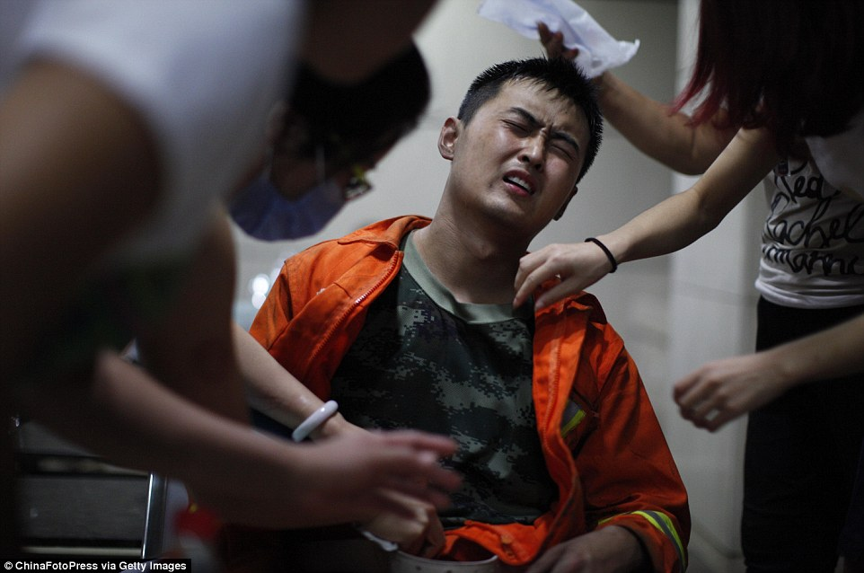 Agony: A firefighter injured in the explosions receives treatment at Teda Hospital in Tianjin, China. At least 11 of his colleagues have died