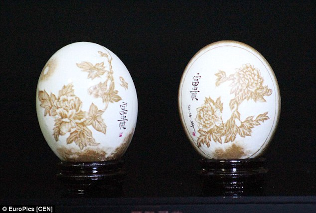 Egg shells artist Zhao Zexi has carved out flowers, above, and then inscribed it with the words 'wealth' in paint