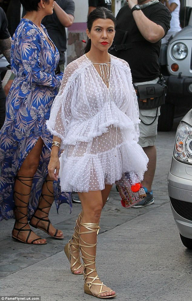 All about the ruffles: Kourtney opted for a flirty tiered dress and gold gladiator sandals
