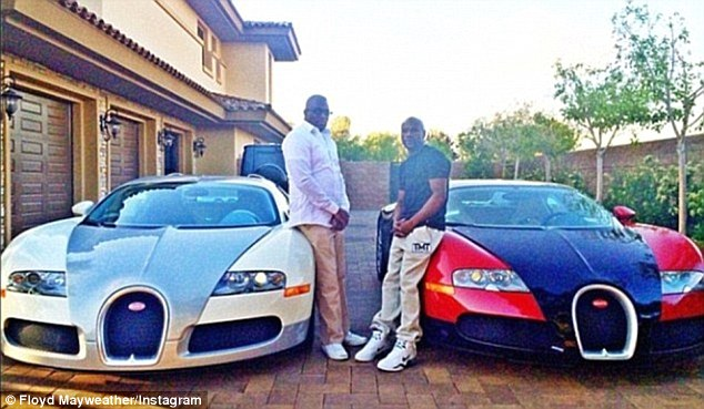 Mayweather (right) shows off two of his Bugattis, which each set him back £1.5m ($2.4m)
