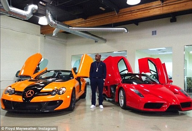 Mayweather while out shopping for cars late last year, flanked by an orange Mercedes and a Ferrari