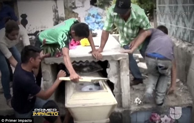 Worst nightmare: Desperate relatives smash into Neysi Perez's concrete tomb a day after she was buried alive by mistake. Her husband raised the alarm after hearing her 'screams for help' while visiting her grave