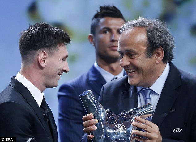 Ronaldo looks on in the background as Platini (right) hands the trophy to Barcelona star Messi (left)