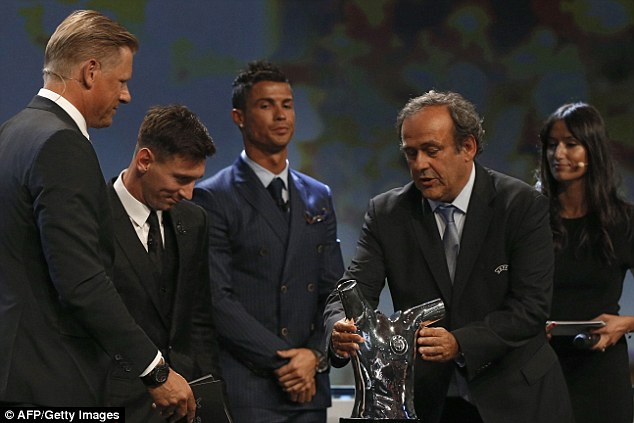 Platini (second right) lifts the trophy to hand over after Messi was announced as the winner