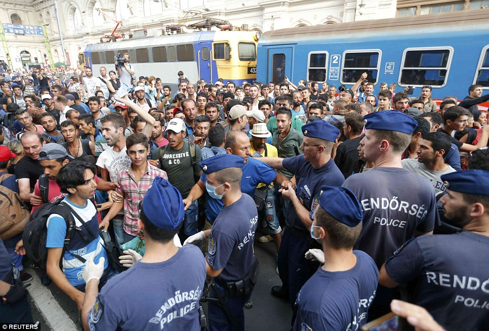 Clashes: Migrants and police pictured at the railway station in Budapest, Hungary, after people were told to leave and it was closed