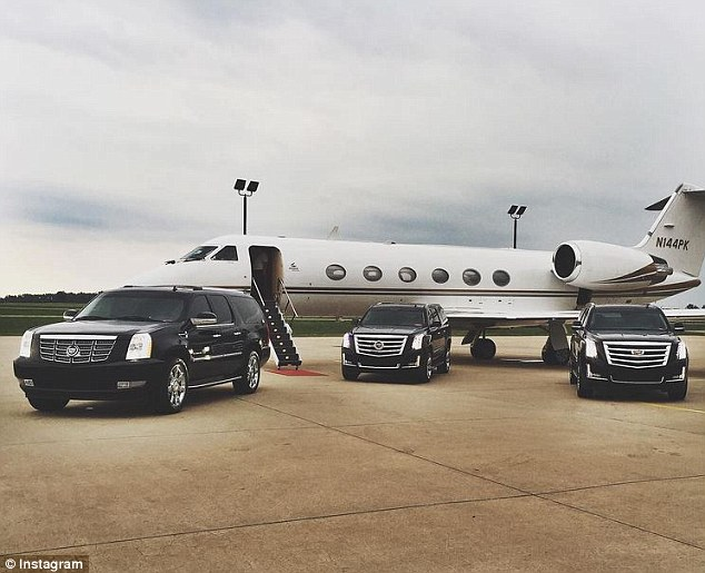 A fleet of Cadillac SUVs and a private jet are seen parked on the tarmac before one of Big Mike's journeys