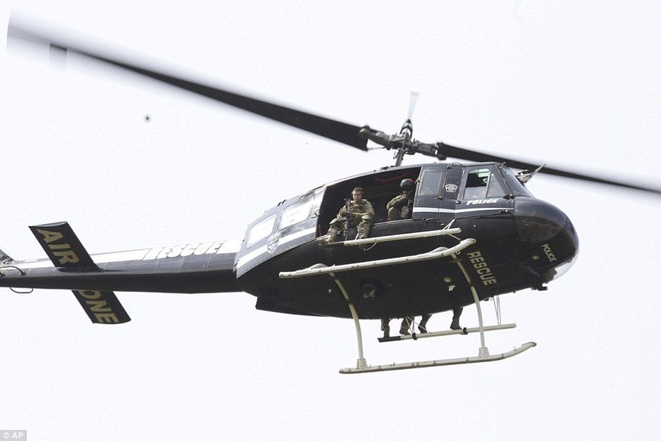 A police helicopter patrols a swampy area near Route 59 and Rollins in Fox Lake, Illinois