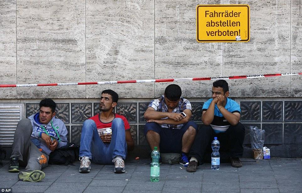 Cansado de esperar: los migrantes se sientan fuera de la estación principal, ya que esperar para el registro en Munich, donde cientos más inmigrantes llegan cada día