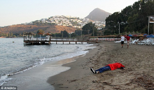 A migrant is pictured washed up on the sand at a beach in Bodrum, which is popular with tourists