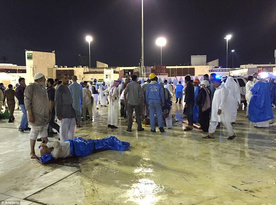Un hombre herido envuelto en unas mentiras impermeables en el suelo en medio de escenas caóticas en La Meca este tardes