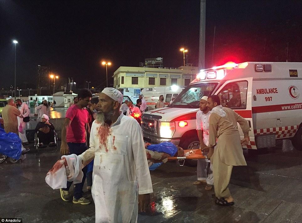 Caminar herido: Un hombre se encuentra en estado de shock, sus ropas manchadas de sangre, mientras que la víctima peor es derribado en una ambulancia