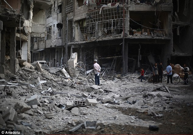 Rubble: Huge piles of rubble are seen following an airstrike in a residential suburb of Damascus