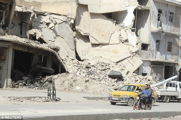 Carnage: Residents drive a motorcycle through Aleppo's al-Saliheen district after an Assad regime airstrike