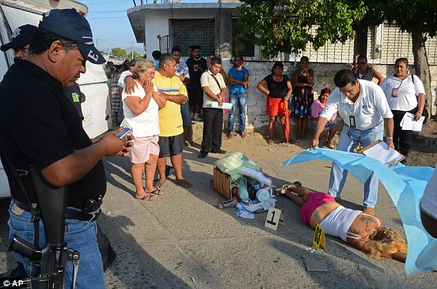 Cut down: Forensic teams in Acapulco, Mexico, cover up the body of a woman who was shot dead while selling coffee on a street corner
