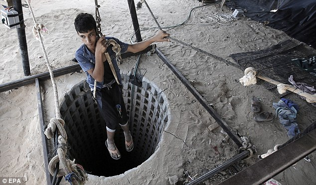 A Palestinian youth shows how to abseil into one of the tunnels on the Gaza side after Egyptian forces flooded smuggling tunnels beneath the border to the Gaza strip, in Rafah, southern Gaza Strip