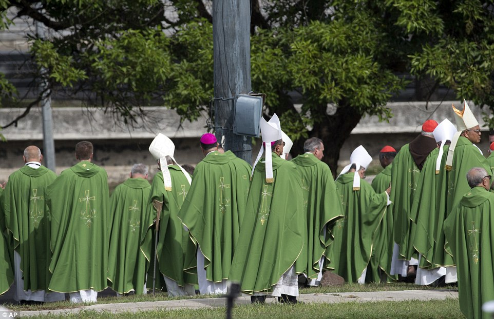 Dressed in their full green robes, clergymen leave after the ceremony by the pope who urged Cubans to take care of their 'brothers and sisters'