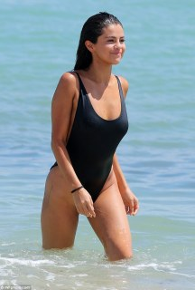 Not shy: The Spring Breakers star's sexy black bathing suit put her toned back and upper thighs on maximal display as she strolled through the bright water