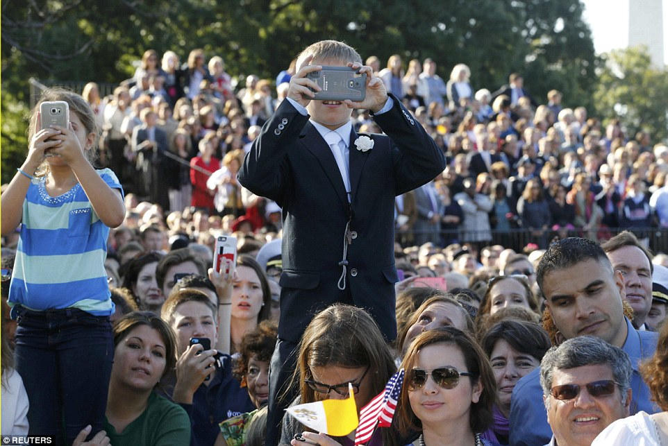 Children take pictures of the pope, who chose to address the crowds in English despite struggling with the language