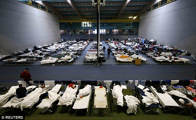 Migrants and refugees rest on beds at an improvised temporary shelter in a sports hall in Hanau, Germany, this week. EU border guard agency Frontex has warned a market in fake Syrian passports has sprung up, particularly in Turkey, to help migrants and refugees enter the EU