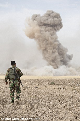 A Kurdish peshmerga fighter watches the smoke plumes from two large bombs dropped by coalition air support to suppress ISIS in the village of Mansoria earlier this afternoon