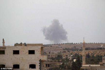 Bombed: Smoke rises from a base controlled by rebels from the Ahrar al-Sham Movement in Idlib, Syria