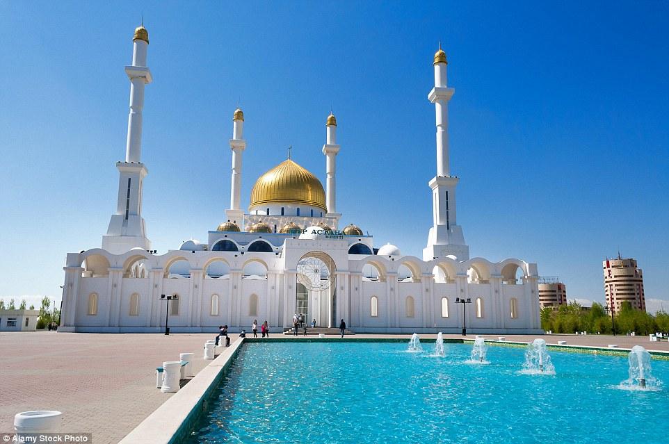 O multi-abobadado Nur-Astana Mesquita em Astana, Cazaquistão tem uma magnífica cúpula de ouro e uma fonte na parte da frente do edifício
