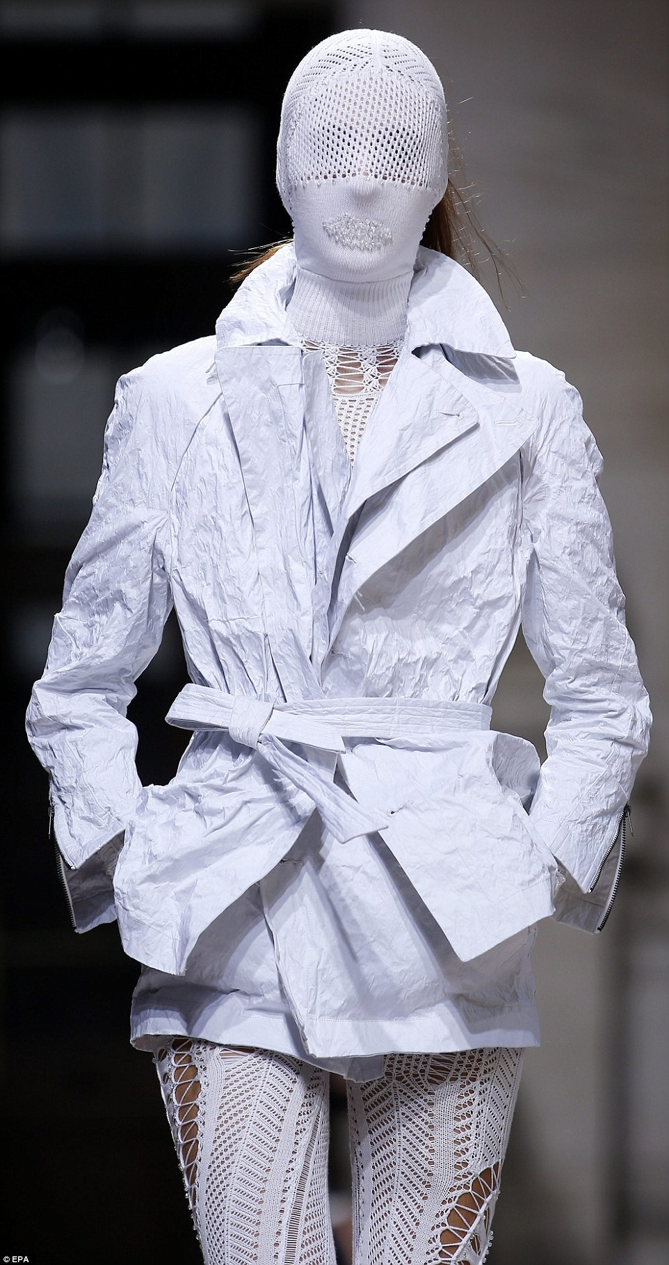A model takes to the runway in a creased blazer-like jacket and vision-restricting mesh mask