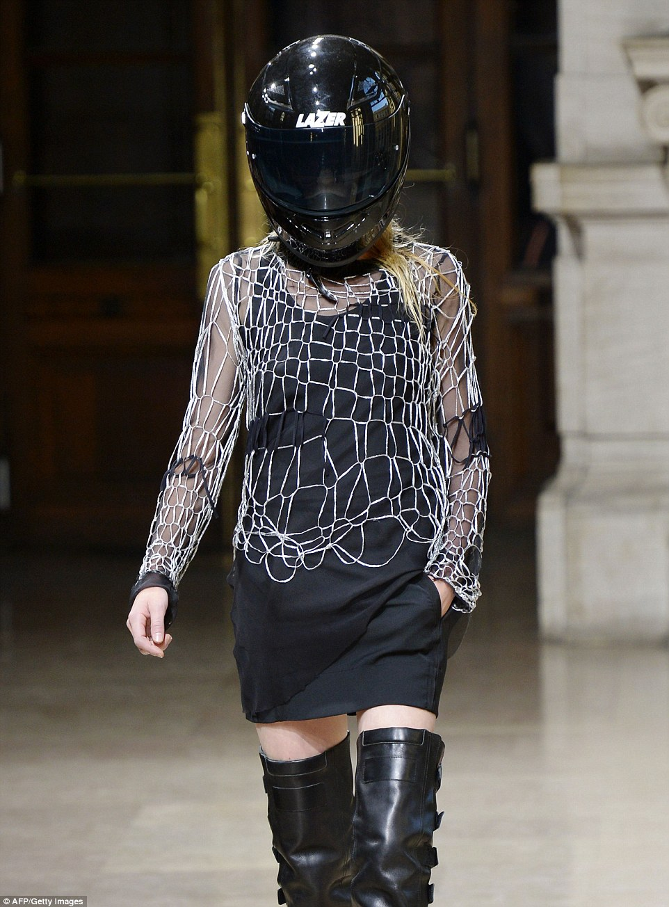 One helmet-clad model at A.F Vandevorst stormed the runways in a white wide-knit jumper and thigh-high leather boots with buckle-detailing along the side