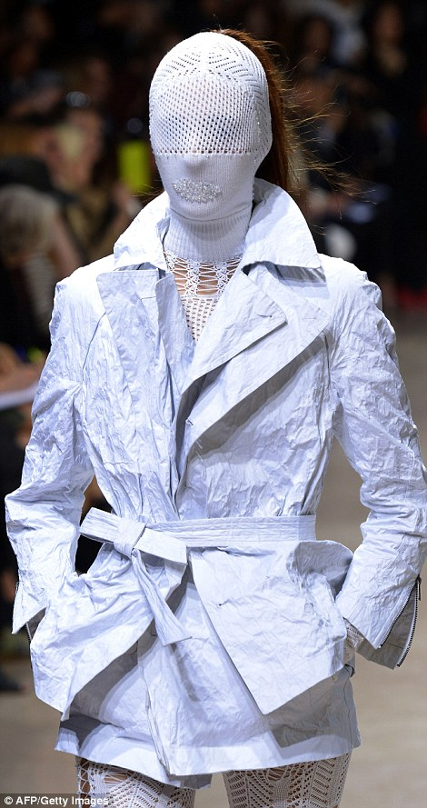 A model strides down the runway in an eye-catching white mesh outfit