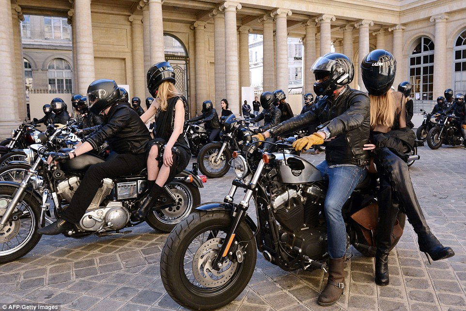 Models cause a scene outside of the presentation by arriving in style on the back of a bike