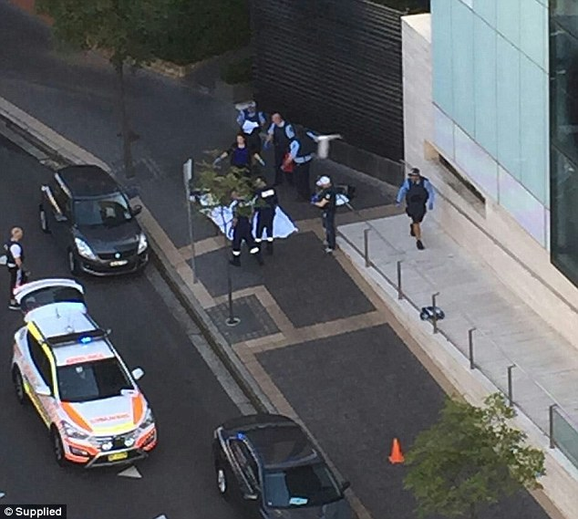 A civilian IT expert working for police is believed to have been shot dead after a lone gunman opened fire outside a force headquarters in Sydney, pictured officers gather around a white sheet covering a body