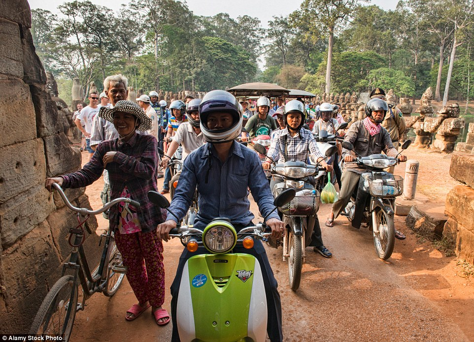 Bicycles, scooters and motorbikes queue up in rush hour traffic at Angkor Wat in Siem Reap, Cambodia