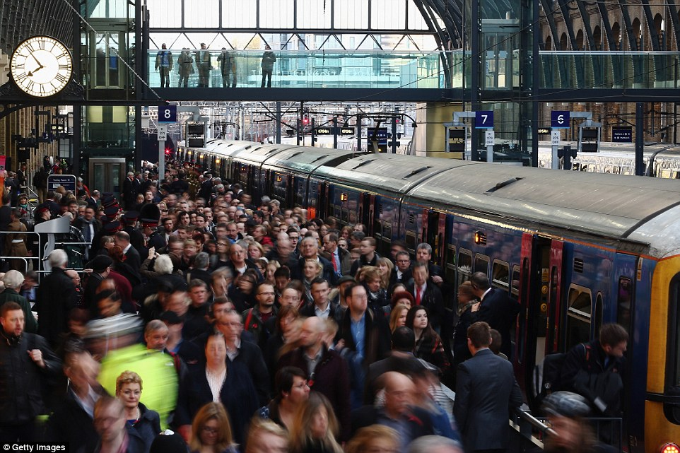 Passengers disembark at King's Cross station during peak times. Commuters are pushed together as they make their way towards the exit