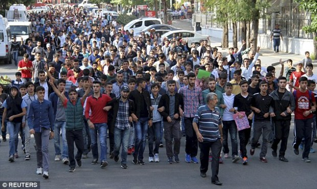 Furious: Turkish Kurdish men shout slogans during a protest, in the southeastern Turkish city of Diyarbakir, against explosions at the peace march today in Ankara