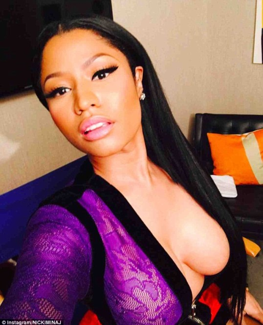 Daring as always:Featuring a purple long sleeved top section and orange skirt with black edging, Nicki wore the gown unzipped to her belly button showing off her gravity defying cleavage