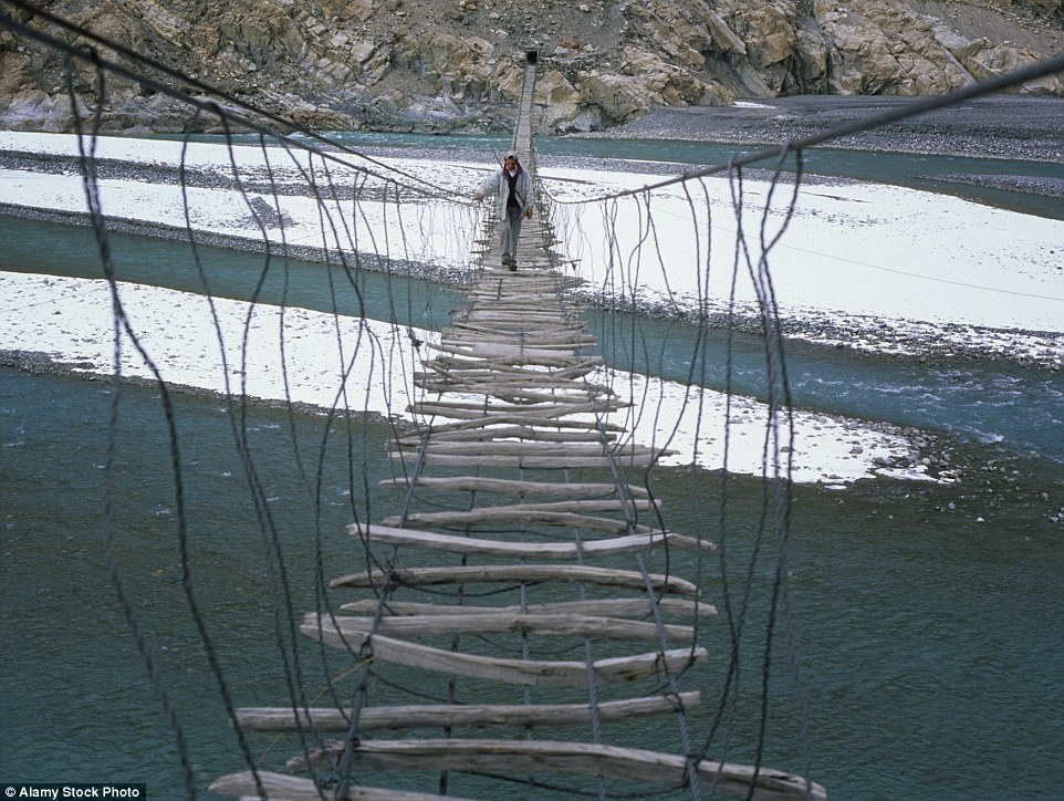 One way of getting across the Hunza River in the Karakoram Mountains of Pakistan is by the rickety Hussaini bridge, which consists of various pieces of wood strapped horizontally
