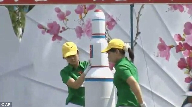 Children are taught that they should be prepared to risk their own life to save the supreme leader, pictured posing with a model of a nuclear missile