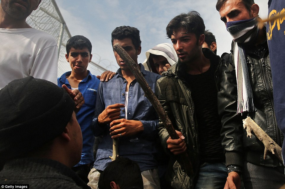 Fighting: Sticks were used as weapons and punches thrown as thousands continued to arrive in makeshift rafts and boats to flee conflict in Iraq, Syria, Afghanistan and other countries