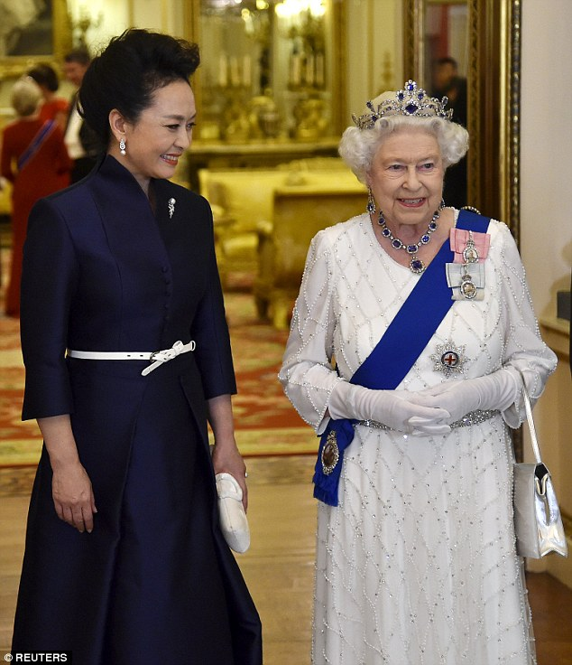 Peng Liyuan, who is on a state visit of the UK with her husband, accompanies Britain's Queen Elizabeth as they arrive for a state banquet at Buckingham Palace in London
