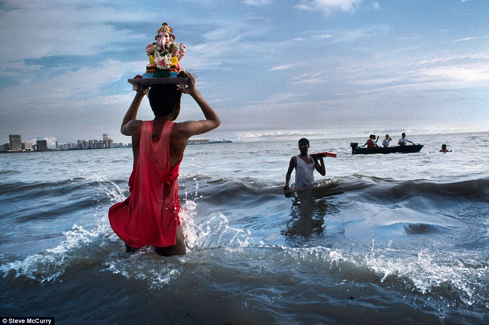 Mumbai, 1993. A devotee carries a statue of Lord Ganesh into the waters of the Arabian Sea during the immersion ritual off Chowpatty beach