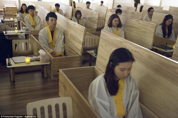 Curious: Depressed pupils sit in their coffins which is are sealed by an 'angel of death' where they lay inside in the dark for ten minutes to reflect on their lives